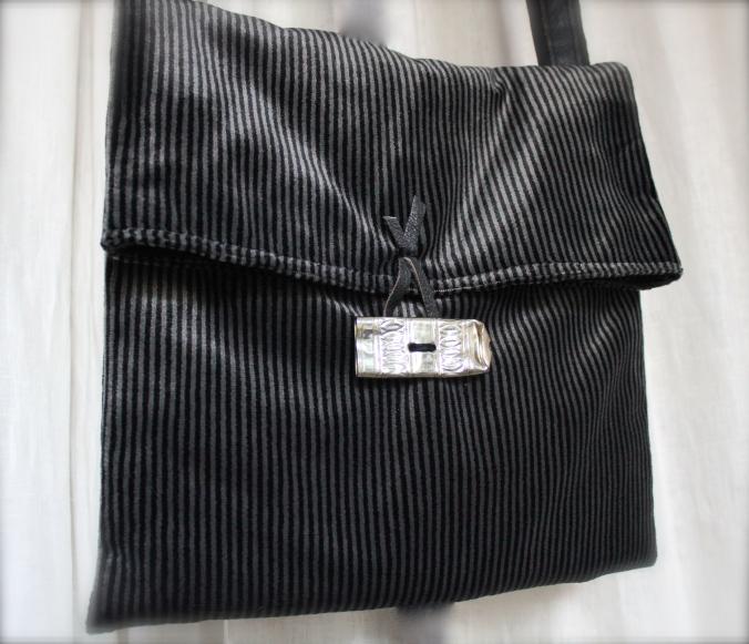 Tracolla in velluto di arredo con grosso bottone fatto da un copre-accendino in argento. Possiede un'ampia tasca interna in lino e pelle. La tracolla è in lino e pelle. Pezzo unico.